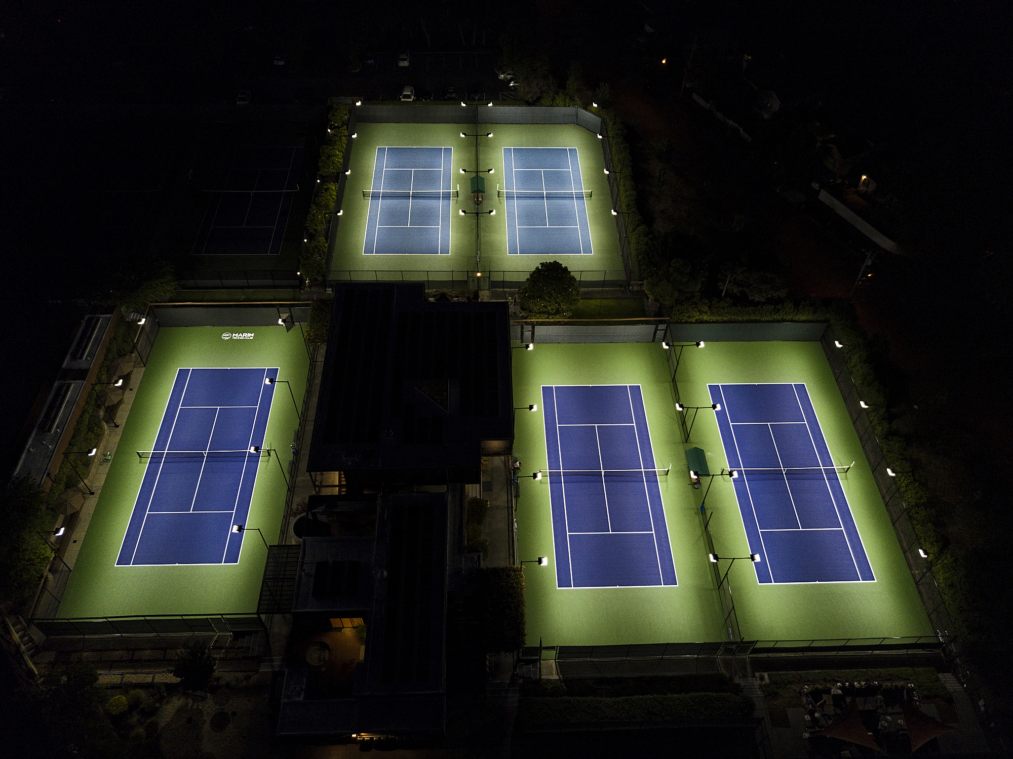 Aerial view of three tennis courts at Marin Country Club lit up by LED Lights installed by ReGreen